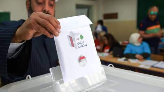 A Lebanese Sunni cleric puts his checked ballot in the box as he casts his vote in the first parliamentary election in nine years, at a polling station in the capital Beirut on May 6, 2018.