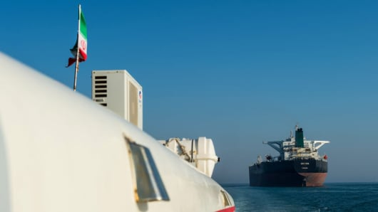 A support vessel maneuvers near the crude oil tanker 'Devon' as it sails through the Persian Gulf towards Kharq Island oil terminal to transport crude oil to export markets in Bandar Abbas, Iran, on Mar. 23, 2018.