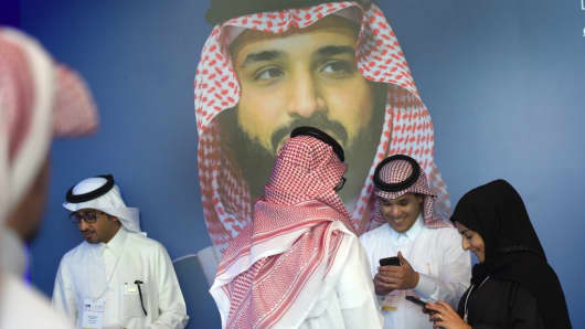 Saudis chat and check their phones in front of a poster of Saudi Crown Prince Mohammed bin Salman