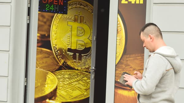 A man passes in front of a Bitcoin exchange shop.