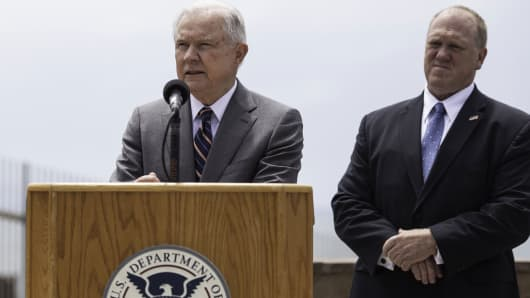 Jeff Sessions, U.S. attorney general, left, speaks as Tom Homan, deputy director of U.S. Immigration & Customs Enforcement (ICE), listens during a press conference regarding immigration policy in San Diego, California, U.S., on Monday, May 7, 2018.