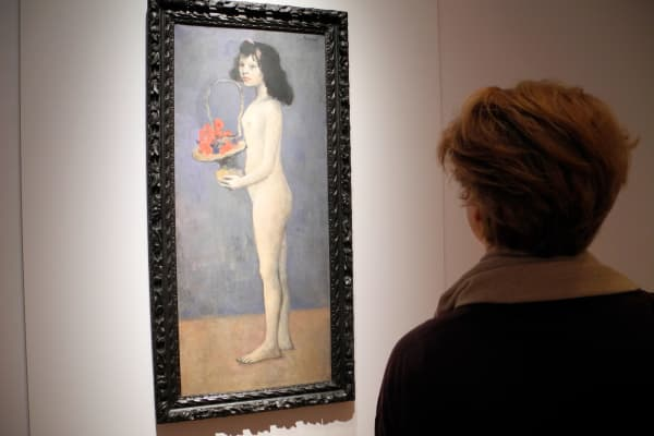 "A woman standing at the Christie's auction house in New York in front of the painting ""Fillette la corbeille fleurie"" by the painter Pablo Picasso. The painting is to be auctioned off as part of the art collection of the late US billionaire David Rockefeller."