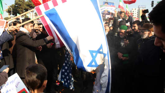 Iranian pro-government supporters burn the Israeli and US flags during a rally in support of the regime after authorities declared the end of deadly unrest, in the city of Mashhad on January 4, 2018.