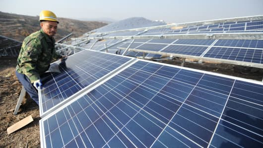 A worker installs polycrystalline silicon solar panels as a terrestrial photovoltaic power project starts in Yantai, Shandong Province of China.
