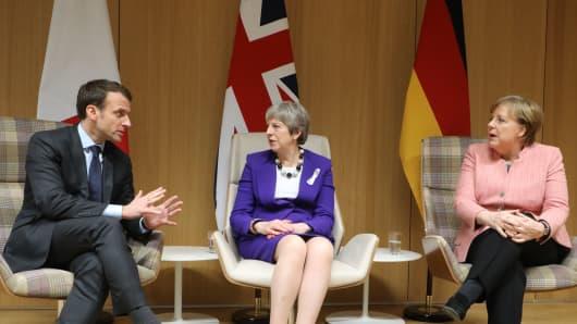 British Prime Minister Theresa May (C), German Chancellor Angela Merkel (R) and French President Emmanuel Macron (L).