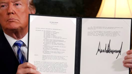 President Donald Trump holds up a proclamation declaring his intention to withdraw from the JCPOA Iran nuclear agreement after signing it in the Diplomatic Room at the White House in Washington, U.S. May 8, 2018.