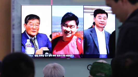 People watch a TV news report on screen, showing portraits of three Americans, Kim Dong Chul, left, Tony Kim and Kim Hak Song, right, detained in the North Korea at the Seoul Railway Station in Seoul, South Korea, Thursday, May 3, 2018.