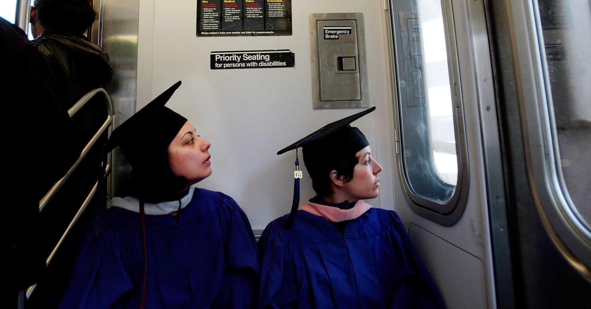 Two New York University graduates ride the subway.