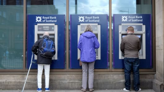 Members of the public use Royal Bank of Scotland cash machines on Princes Street, Edinburgh on April 27, 2018.
