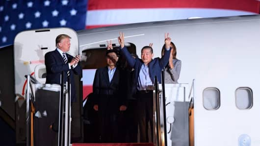 US President Donald Trump (L) applauds as US detainee Kim Dong-chul (2nd R) gestures upon his return with Kim Hak-song (C) and Tony Kim (behind) after they were freed by North Korea, at Joint Base Andrews in Maryland on May 10, 2018.