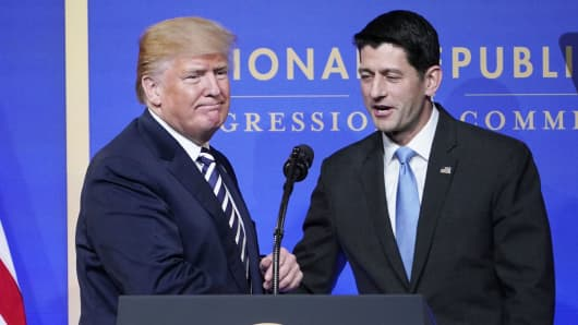 House Speaks Paul Ryan greets US President Donald Trump as he arrives on stage to speak at the National Republican Congressional Committee March Dinner at the National Building Museum on March 20, 2018 in Washington, DC.