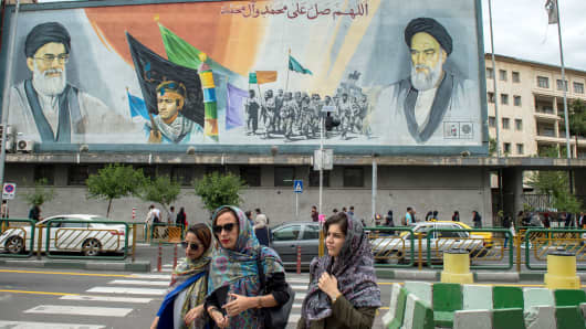 Women cross a street near a giant political mural depicting Ayatollah Ali Khamenei, Iran's supreme leader, left, and Ruhollah Khomeini, founder of the Islamic republic of Iran, in Tehran, Iran, on Wednesday, May 9, 2018.