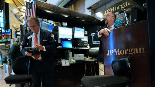 Traders work at the JPMorgan Chase & Co. booth on the floor of the New York Stock Exchange (NYSE) in New York.