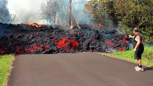 In this photo taken from video an unidentified man gets close to a lava flow advancing down a road in the Leilani Estates subdivision near Pahoa on the island of Hawaii Monday, May 7, 2018.