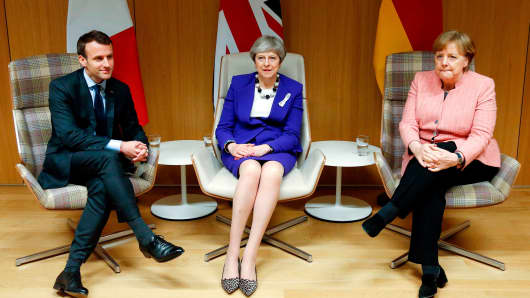 British Prime Minister Theresa May (C), German Chancellor Angela Merkel (R) and French President Emmanuel Macron (L) give a press conference following a meeting on the sidelines of the European Union leaders summit in Brussels, on March 22, 2018.