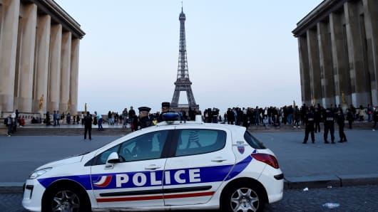 Policemen stand near a vehicle on the place du Trocadero in Paris on April 21, 2017.