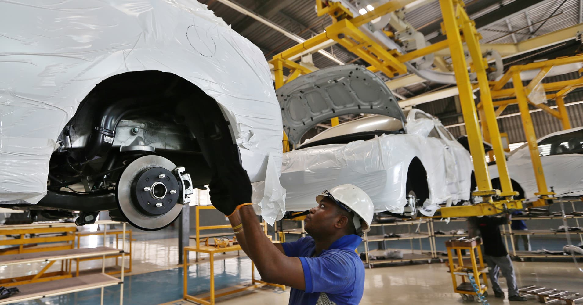 A worker fits parts to the underside of a raised Hyundai Motor Co. Accent automobile on a production line at Stallion Group vehicle assembly plant in Lagos, Nigeria, on February 17, 2016.