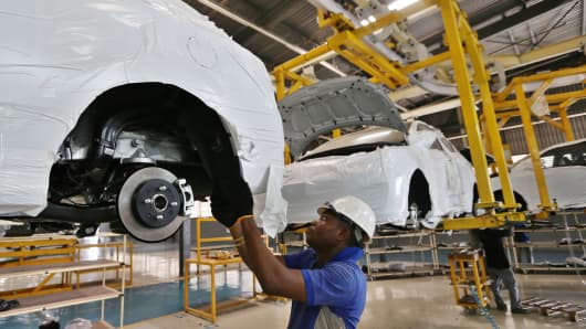 A worker fits parts to the underside of a raised Hyundai Accent car at a vehicle assembly plant in Lagos, Nigeria, on February 17, 2016.