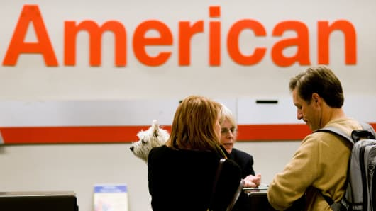 Passengers holding their dog Neko, check in for a flight with an American Airlines agent at Dallas-Fort Worth International Airport in Dallas, Texas.