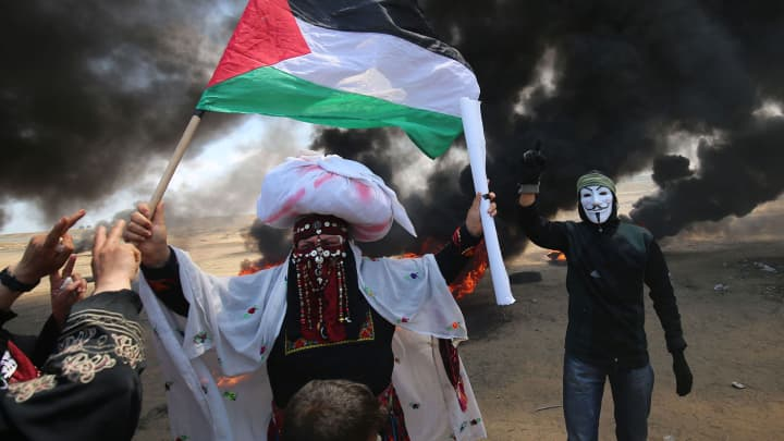 A Palestinian man holding his national flag walks in the smoke billowing from burning tyres next to a protester wearing an Anonymous mask during clashes with Israeli forces along the border with the Gaza strip east of Khan Yunis on May 14, 2018, as Palestinians protest over the inauguration of the US embassy following its controversial move to Jerusalem.