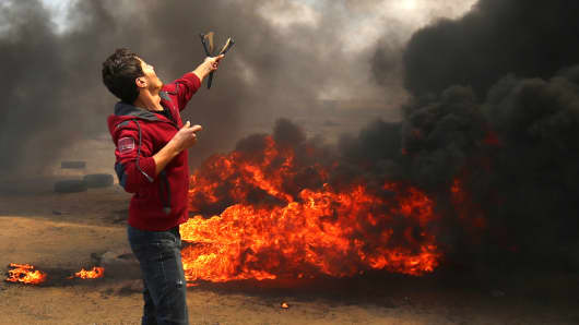 A Palestinian man uses a slingshot during clashes with Israeli forces along the border with the Gaza strip east of Khan Yunis on May 14, 2018, as Palestinians protest over the inauguration of the US embassy following its controversial move to Jerusalem.