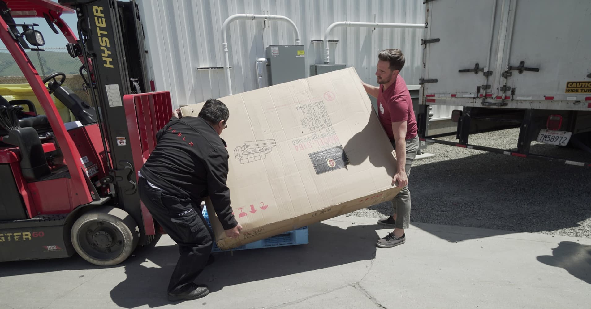 YouTuber Ben Sullins (right) delivers a brand new couch to the Tesla factory in Fremont, California on May 1, 2018.