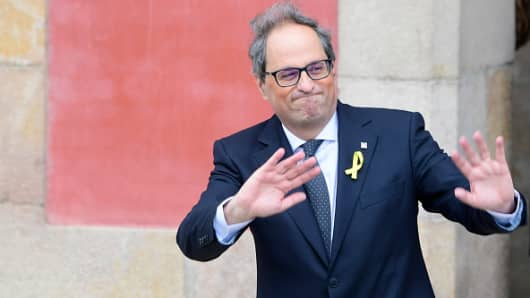 The newly elected Catalan regional president Quim Torra waves as he leaves the Catalan parliament.