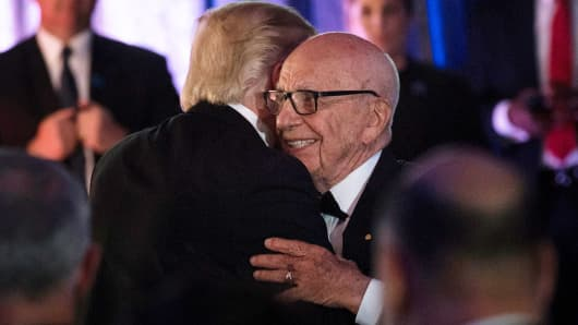 President Donald Trump (L) is embraced by Rupert Murdoch, Executive Chairman of News Corp, during a dinner to commemorate the 75th anniversary of the Battle of the Coral Sea during WWII onboard the Intrepid Sea, Air and Space Museum May 4, 2017 in New York.