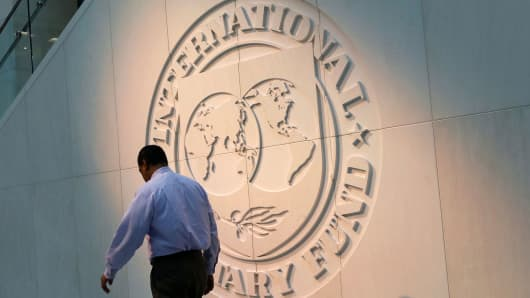 A man walks past the International Monetary Fund (IMF) logo at its headquarters in Washington, DC.