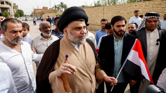 Iraqi Shiite cleric and leader Moqtada al-Sadr (C-L) shows his ink-stained index finger and holds a national flag while surrounded by people outside a polling station in the central holy city of Najaf on May 12, 2018 as the country votes in the first parliamentary election since declaring victory over the Islamic State (IS) group.