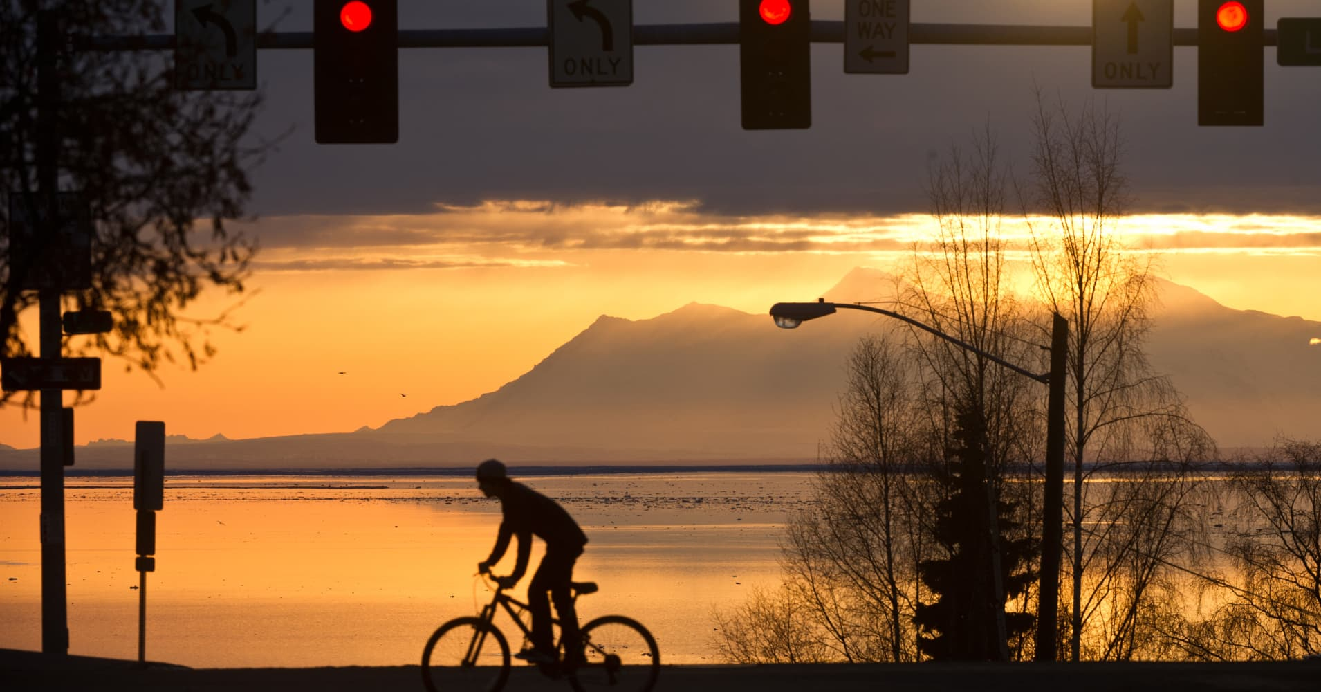 A cyclist rides his bike as a late-day sun peeks through the clouds over Cook Inlet in downtown Anchorage, Alaska, on Tuesday, April 2, 2013.
