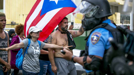 A demonstrator holds a Puerto Rican flag while being confronted by riot police officers during a protest against austerity measures in the Hato Rey neighborhood of San Juan, Puerto Rico, on Tuesday, May 1, 2018.