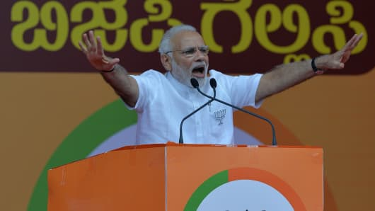 Indian Prime Minister Narendra Modi gestures to supporters during an election campaign rally in Bangalore on May 3, 2018.