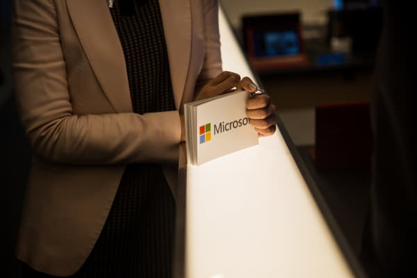 An employee holds cards displaying the logo of Microsoft Corp.