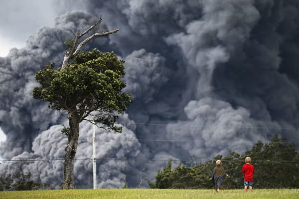 Boys look on while playing at a golf course as an ash plume rises in the distance from the Kilauea volcano on Hawaii's Big Island on May 15, 2018 in Hawaii Volcanoes National Park, Hawaii.