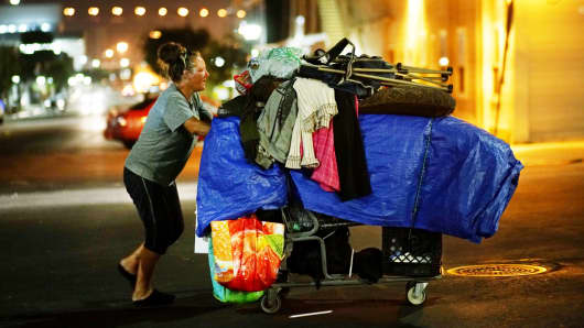 A homeless woman walks with her belongings in the East Village area of Downtown San Diego, California.