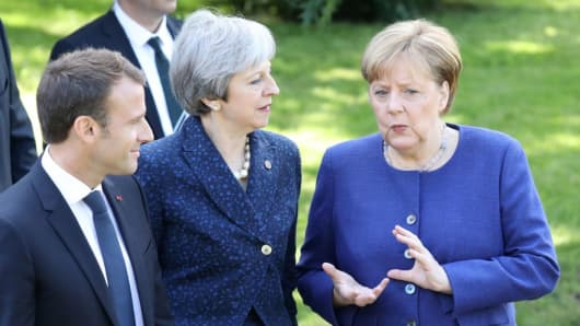 French President Emmanuel Macron (L), Britain's Prime Minister Theresa May (C) and German Chancellor Angela Merkel take a moment to discuss as they walk together during an EU-Western Balkans Summit in Sofia on May 17, 2018.