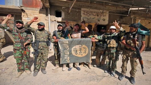 Fighters of Hashed Al-Shaabi (Popular Mobilization units) flash the victory gesture as they hold upside down a banner bearing the logo of the Islamic State (IS) group, during the advance in the town of Tal Afar, west of Mosul, after the Iraqi government announced the launch of the operation to retake it from IS control, on August 26, 2017.