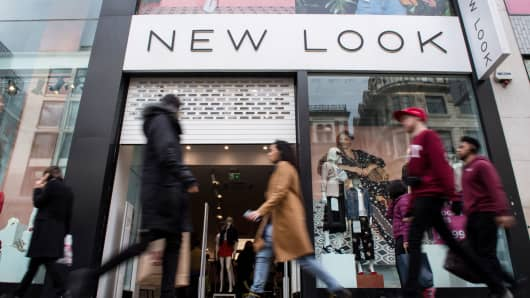 Pedestrians walk past a New Look shop on Oxford Street in London, England.