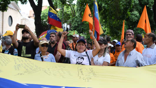 Protesters seen marching toward the OEA while holding the Venezuelan flag at the demonstration.