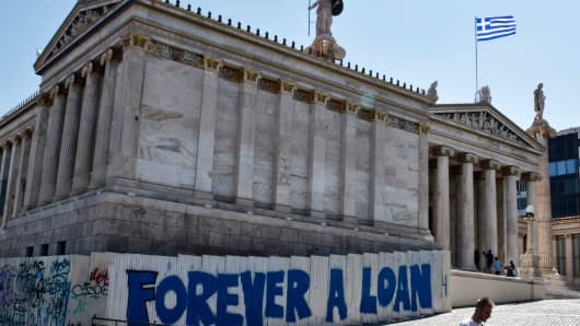 A woman walks past a graffiti refering to the Greek debt and reading 'Forever a loan' outside the Academy of Athens building on August 28, 2017.