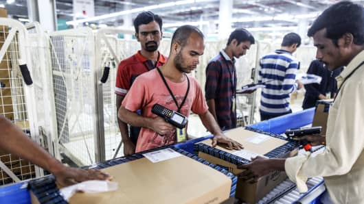 Employees prepare packages for shipment on the conveyor belt at the Amazon.com fulfillment center in Hyderabad, India.