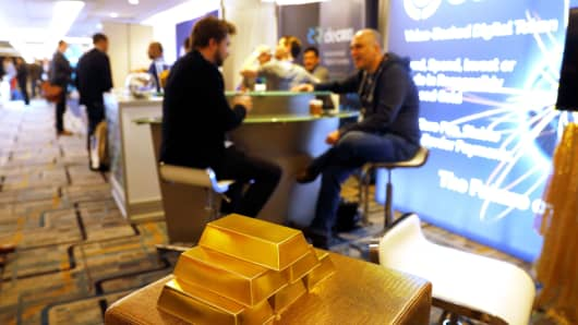 Imitation gold bars are seen displayed at a vendor's booth on the floor of the Consensus 2018 blockchain technology conference in New York City, May 16, 2018.