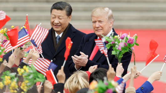 Chinese President Xi Jinping and President Donald Trump greet attendees waving American and Chinese national flags during a welcome ceremony outside the Great Hall of the People in Beijing, China, on Nov. 9, 2017.