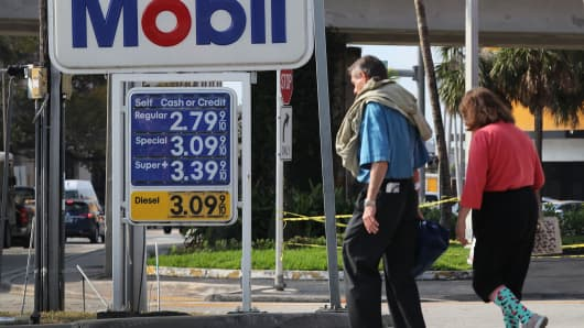A sign displaying the price of gasoline per gallon is seen at a Mobil gas station in Miami.