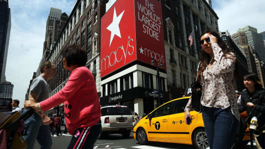 Pedestrians walk by Macy's flagship store in Herald Square in New York, New York.