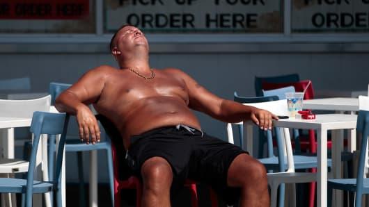 A man sunbathes on the boardwalk at Coney Island Beach.