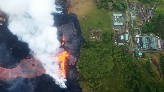 Lava erupts and flows from a Kilauea volcano fissure, near to the Puna Geothermal Venture (PGV) plant (TOP R), on Hawaii's Big Island on May 21, 2018 near Pahoa, Hawaii. The plant, currently shut down in the wake of encroaching volcanic activity, provides electricity to around 25 percent of the island.
