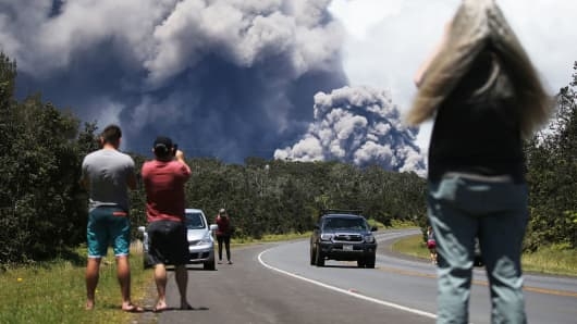 Tourists watch ash plume rise from the Kilauea volcano on Hawaii's Big Island on May 15, 2018 in Volcano, Hawaii.