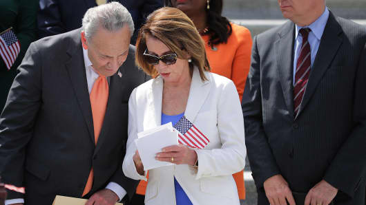 Senate Minority Leader Chuck Schumer (D-NY) (L) and House Minority Leader Nancy Pelosi (D-CA) look over notes on May 21, 2018.